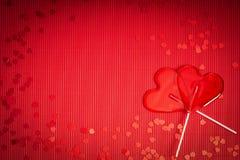 De achtergrond van de valentijnskaartendag met rood geribbeld document met twee lollys voor minnaars royalty-vrije stock afbeelding