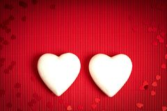 De achtergrond van de valentijnskaartendag met rood geribbeld document met twee witte storaxschuimharten voor minnaars stock foto's