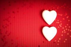 De achtergrond van de valentijnskaartendag met rood geribbeld document met twee witte storaxschuimharten voor minnaars stock afbeelding