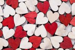 De achtergrond van de valentijnskaartendag met witte eind rode harten op houten achtergrond stock afbeeldingen