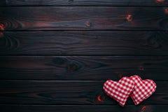 De achtergrond van de valentijnskaartendag Twee geruite stoffenharten op donker w Royalty-vrije Stock Afbeelding