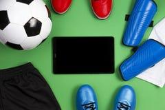 De achtergrond van de voetbalvoetbal Tabletcomputer met voetbalbal, blauwe laarzen, cleats, witte t-shirt en zwarte borrels  royalty-vrije stock fotografie