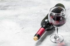 De achtergrond van de wijn Een fles rode wijn met een glas royalty-vrije stock foto
