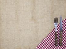 De achtergrond voor het menu Tafelkleed van jute, vork, mes voor lapje vlees en servet Wordt gebruikt om een menu voor lapje vlee Royalty-vrije Stock Afbeeldingen
