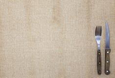 De achtergrond voor het menu Tafelkleed van jute, vork, mes voor lapje vlees en servet Wordt gebruikt om een menu voor lapje vlee Royalty-vrije Stock Foto's