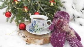 De achtergrond voor het nieuwe jaar van Kerstboom vertakt zich, ballen en klokken, koppen van koffie en warme vuisthandschoenen Stock Fotografie