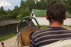 De achtergrondmeningsmens stelt een landelijke kar met een paard, een museum van in werking het landelijke leven royalty-vrije stock foto's
