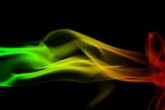 de achtergrondrookkrommen en golfreggae kleuren groen, geel, rood gekleurd in vlag van reggaemuziek stock foto