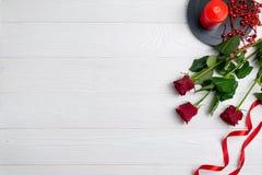 De achtergrondsamenstelling van de groetkaart of met rode rozen en kaars met ruimte voor tekst stock afbeelding