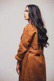 De achterkant van de foto van de manierstudio van schitterende sensuele vrouw met donker recht haar draagt elegante bruine laag Stock Foto's