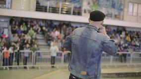 De achterkant van de mens in hoed spreekt in microfoon met mensen in skatepark uitdaging competition gastheer stock videobeelden