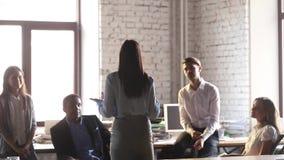 De achtermening bij vrouwelijke leider motiveert team vertelt groot nieuws stock footage