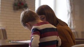De achtermening een charmante jonge moeder en een zoon zit bij een lijst stock videobeelden