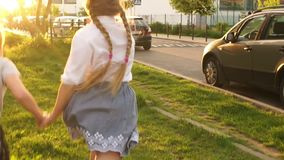 De achtermening, twee meisjesschoolmeisjes komt de afstand tegen door het stadspark Gelukkige kinderjaren, schoolvriendschap, rug stock footage