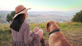 De achtermening van aanbiddelijk meisje met hoed zit op de weide met haar leuke hond stock videobeelden