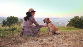 De achtermening van aanbiddelijk meisje met hoed zit op de weide met haar leuke hond stock video