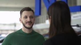 De achtermening van Aantrekkelijke vrouwelijke autohandelaar spreekt aan geinteresseerde klant over nieuw automobiel model stock videobeelden