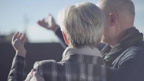 De achtermening van bejaarden koppelt het bekijken de hemel en het communiceren met elkaar Rijp echtpaar in openlucht stock video