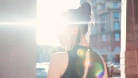 De achtermening van een aantrekkelijke donkerbruine vrouw in een elegante uitrusting die van het gebouw, draaien aan camera opsta stock footage