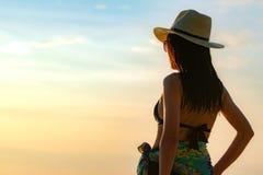 De achtermening van gelukkige jonge Aziatische vrouw in zwarte zwempak en strohoed ontspant en geniet van vakantie bij tropisch p royalty-vrije stock foto's