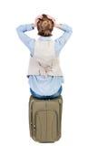 De achtermening van geschokte vrouw in vest zit op een koffer Stock Foto's