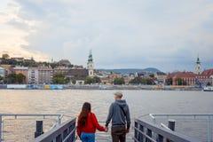 De achtermening van het aantrekkelijke paar in liefde houdt handen en geniet van het landschap van Rivier Donau in Boedapest Royalty-vrije Stock Foto's