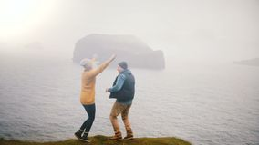 De achtermening van het jonge gelukkige paar bevindt zich op de kust van een overzees en het springen van vreugde, koesterend in  stock video