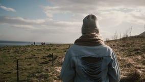 De achtermening van het jonge modieuze vrouw lopen door het gebied op de paarden bewerkt Vrouwelijke het besteden tijd op de aard stock videobeelden