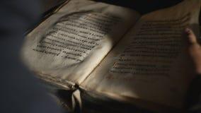 De achtermening van iemand doorbladert oud boek stock video