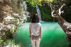 De achtermening van jonge vrouw geniet van waterval op mooi meer Royalty-vrije Stock Afbeelding