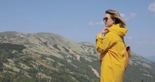 De achtermening van Kaukasische vrouwelijke wandelaar in gele regenjas bevindt zich in de bergen stock video