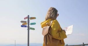 De achtermening van Kaukasische vrouwelijke wandelaar in gele regenjas bevindt zich in de bergen met een in hand kaart stock videobeelden