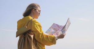 De achtermening van Kaukasische vrouwelijke wandelaar in gele regenjas bevindt zich in de bergen met een in hand kaart stock footage