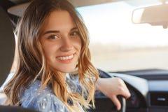De achtermening van mooie glimlachende vrouw met brede glimlach, heeft aantrekkelijk eruit zien, zit bij wiel in auto, heeft onde stock fotografie