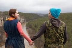 De achtermening van paarwandelaars die zich op de rand van een klip over de bergrivier bevinden en houdt handen elkaar Stock Afbeeldingen