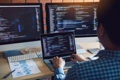 De achtermening van softwareontwikkelaars zit ernstige analyserende gegevens over het computerscherm stock afbeeldingen