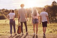 De achtermening van vriendschappelijke klasgenoten recreat buiten tijdens zonnig weer, heeft gang over weide, gebruiksgitaar voor royalty-vrije stock foto