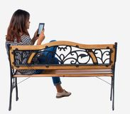 De achtermening van vrouwenzitting op bank en bekijkt het scherm de tablet royalty-vrije stock afbeeldingen