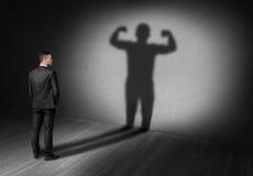 De achtermening van zakenman kijkt aan schaduw met sterk voortaan zijn vertoning stock foto's
