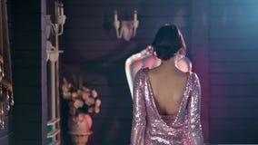 De achtermenings modieuze vrouw vervuilt het tonen van verbazende glamourkleding met naakte rug stock footage