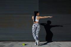 De achtermenings sportieve vrouw met perfect cijfer en de billen geven het uitoefenen tegen muur met exemplaarruimte voor gestalt Stock Fotografie