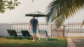 De achtermenings succesvolle mannelijke toerist gaat langzaam aan stoelen en omheining naar boven om van epische het strandmening stock video