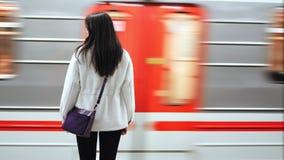 De achtermenings toevallige jonge vrouw in metro tijdens middelgrote aankomsttrein snakt schot stock footage