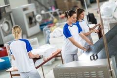 De achtermeningsarbeider keurt gestreken textiel goed stock afbeeldingen