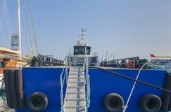 De achtersteven van het schip die zich in die de haven bij de muur van de kadeligplaats, met een ladder bevinden, tegen de achter stock foto