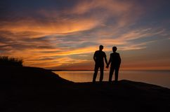 De achterverlichting van paarholding overhandigt agains rode zonsondergang, zonnestralen royalty-vrije stock foto's