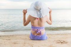 De achterzitting van het vrouwenmeisje op tropisch strand royalty-vrije stock foto