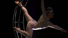 De acrobaat in een kostuum boog elegant op een roterend ontwerp in de vorm van een maand Zwarte achtergrond Langzame Motie stock footage
