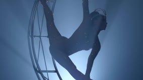 De acrobaat in een kostuum boog elegant op een roterend ontwerp in de vorm van een maand Zwarte rookachtergrond Langzame Motie stock videobeelden