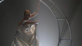 De acrobaat in een witte kleding voert bewegingen op een maan van de metaalbouw uit Rook achtergrond Langzame Motie Sluit omhoog stock videobeelden
